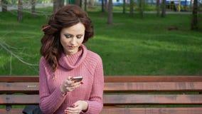 El cardán tiró de la muchacha adolescente femenina que hablaba en el teléfono que se sentaba en banco en el día soleado de la pri almacen de metraje de vídeo