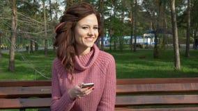El cardán tiró de la muchacha adolescente femenina que hablaba en el teléfono que se sentaba en banco en el día soleado de la pri metrajes