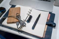 El cargador de batería del bolsillo y la pluma en el cuero azul organizan foto de archivo libre de regalías