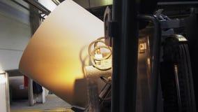 El cargador de la carretilla elevadora transporta el rollo de la cartulina en almacenamiento de la planta almacen de video
