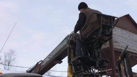 El cargador de la garra del camión descarga los pedazos de la madera del camión pesado en la instalación de la serrería almacen de metraje de vídeo