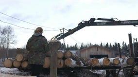 El cargador de la garra del camión descarga registros de la madera del camión pesado en la instalación de la serrería almacen de metraje de vídeo