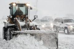 El cargador de la rueda de la parte frontal quita nieve del camino durante la tormenta del invierno de las nevadas fuertes, visib fotos de archivo libres de regalías