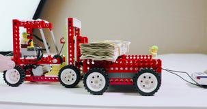 El cargador del constructor del ` s de los niños sumerge una pila de dinero en la carrocería metrajes