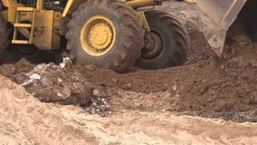 El cargador grande amarillo de la construcción nivela un trozo de tierra para la construcción y recoge la tierra en un cubo, indu almacen de metraje de vídeo