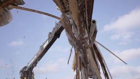 El cargador industrial de la garra coge los pedazos de la madera de construcción del camión pesado en la serrería metrajes