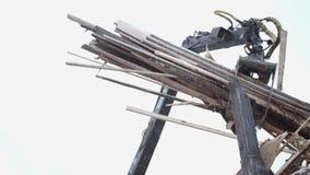 El cargador pesado de la garra descarga los pedazos de madera del camión pesado en la producción de la serrería almacen de video