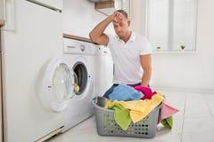 El cargamento cansado del hombre viste en la lavadora imagenes de archivo
