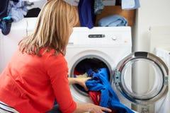 El cargamento de la mujer viste en la lavadora Imágenes de archivo libres de regalías