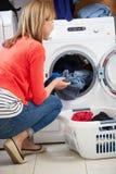 El cargamento de la mujer viste en la lavadora Foto de archivo libre de regalías
