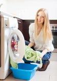 El cargamento de pelo largo de la mujer viste en la lavadora Fotos de archivo libres de regalías