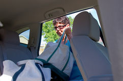 El cargamento mayor de la mujer empaqueta en un vehículo Fotografía de archivo libre de regalías