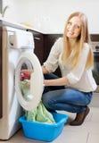 El cargamento rubio feliz de la mujer viste en la lavadora Imágenes de archivo libres de regalías