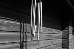 El carillón de viento monocromático del metal está en el edificio de madera foto de archivo
