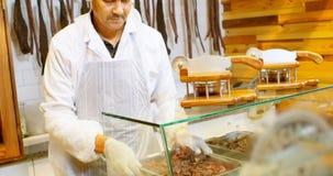 El carnicero arregla la carne en la bandeja en la vitrina 4k almacen de metraje de vídeo