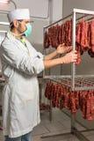 El carnicero controla la salchicha Imágenes de archivo libres de regalías