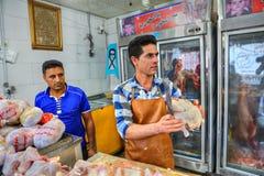 El carnicero iraní corta la carne del pollo de las porciones, Bandar Abbas, Hormoz Imágenes de archivo libres de regalías