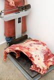 El carnicero pesa la carne Imagen de archivo