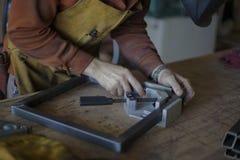 El carpintero ajusta el metal que enmarca según asiento del taburete Imágenes de archivo libres de regalías