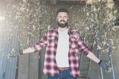 El carpintero barbudo feliz joven del inconformista del hombre en vidrios de la construcción se coloca en taller Desde arriba del Imagen de archivo