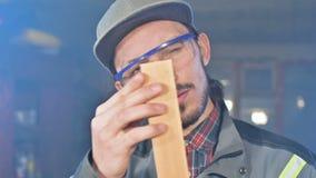 El carpintero barbudo joven concentrado en gafas y un casquillo comprueba el objeto para saber si hay conveniencia mientras que l almacen de video