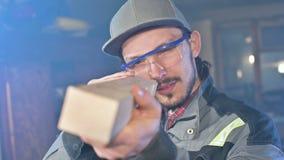 El carpintero barbudo joven concentrado en gafas y un casquillo comprueba el objeto para saber si hay conveniencia mientras que l metrajes