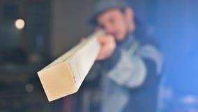 El carpintero barbudo joven concentrado en un casquillo comprueba el objeto para saber si hay conveniencia mientras que la lleva  almacen de video