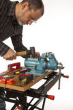 El carpintero con la herramienta en un fondo blanco. Imagen de archivo libre de regalías
