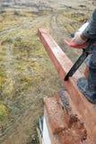 el carpintero con una motosierra hace bebió en una construcción del haz de madera de casas imagen de archivo