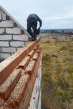 el carpintero con una motosierra hace bebió en una construcción del haz de madera de casas foto de archivo