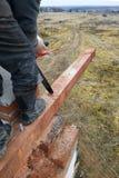 el carpintero con una motosierra hace bebió en una construcción del haz de madera de casas fotos de archivo