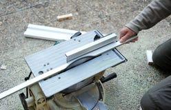 El carpintero cortando con un disco vio un perfil de la madera blanca Foto de archivo
