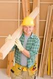 El carpintero de la manitas maduro lleva la viga de madera Fotografía de archivo libre de regalías