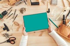 El carpintero de sexo femenino usando la tableta digital, imita encima de la pantalla imagenes de archivo