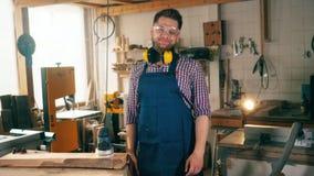 El carpintero de sexo masculino está sonriendo en la cámara en la carpintería almacen de video