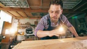 El carpintero de sexo masculino está soplando las virutas de la madera Artesano que trabaja en carpintería almacen de video