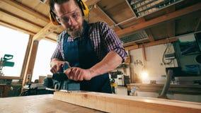 El carpintero de sexo masculino utiliza una herramienta mientras que trabaja con madera Funcionamiento mayor del carpintero metrajes
