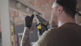 El carpintero en casquillo negro y guantes con los tatuajes en los brazos que ponen el pegamento en el marco de madera para el es almacen de video
