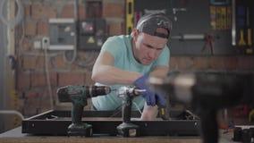 El carpintero en casquillo negro y guantes que ponen el pegamento en el marco de madera El hombre usando el arma de pegamento del almacen de metraje de vídeo