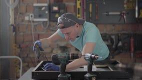 El carpintero en casquillo negro y guantes que ponen el pegamento en el marco de madera El hombre usando el arma de pegamento del almacen de video