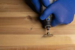 El carpintero en guantes protectores azules maneja el dremel de madera imágenes de archivo libres de regalías