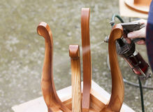El carpintero está cubriendo el taburete por la laca Imagen de archivo libre de regalías