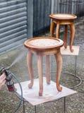 El carpintero está cubriendo el taburete por la laca Imagenes de archivo