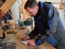 El carpintero está dibujando en su taller Imagen de archivo