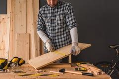 El carpintero está midiendo el tablón de madera de pino foto de archivo