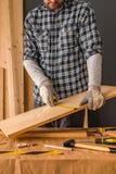 El carpintero está midiendo el tablón de madera de pino imagenes de archivo
