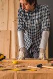 El carpintero está planeando proyecto de la artesanía en madera en taller imagenes de archivo