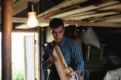El carpintero evalúa la calidad del tablero previsto El empresario evalúa su trabajo en el taller imagenes de archivo