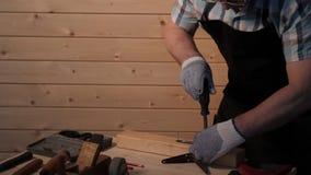 El carpintero mayor aprieta el tornillo almacen de metraje de vídeo