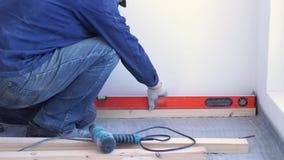 El carpintero principal monta el piso de madera de pino - suelo respetuoso del medio ambiente retraso que atornilla al hormig?n metrajes